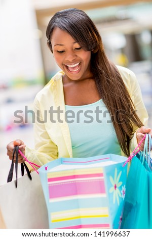 Surprised shopping woman looking into a bag - stock photo