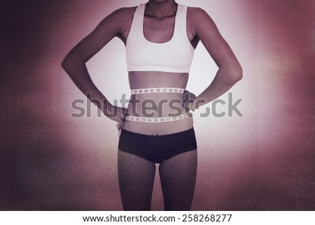 Surprised slim woman measuring her waist against black wall - stock photo