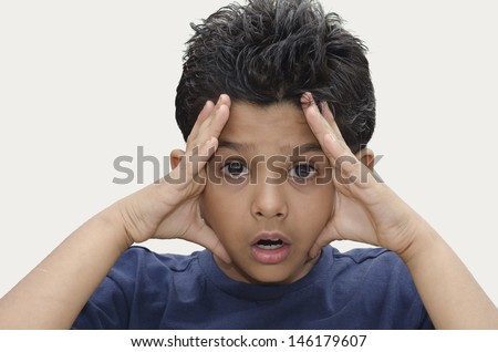 surprised south Asian Indian eight year old boy with an anxious face expression. - stock photo