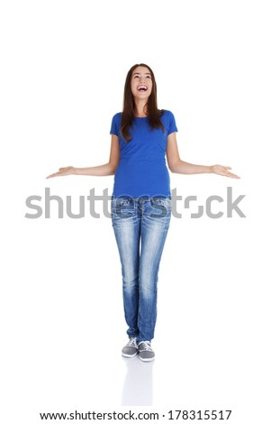 Surprised teen girl with outstretched arms looking up on copy space. Isolated on white. - stock photo
