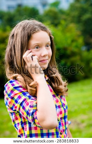 Surprised teenage girl in casual clothes speaking by cell phone, in sunny day in summer park. Girl using smartphone. Teenage girl holding smartphone in her hand - stock photo