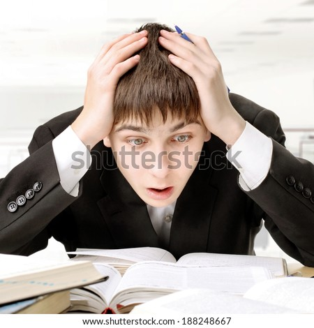 Surprised Teenager at the School Desk studying hard for the Exam - stock photo