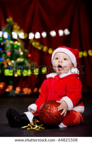 Surprised toddler having large Christmas ball in hands - stock photo