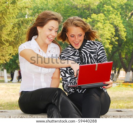 surprised two young girlfriends looking in laptop - stock photo