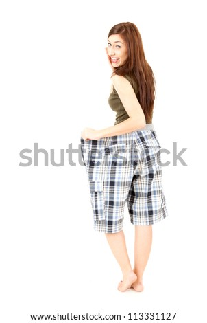 surprised weight lost woman in too big pants, white background - stock photo