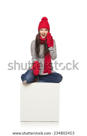 Surprised winter woman wearing knitted warm red scarf and hat sitting on big white box and pointing at it - blank copy space, over white background - stock photo