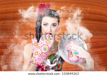 Surprised woman cook lifting lid of a funny recipe inside kitchen interior. Prepare food at home - stock photo