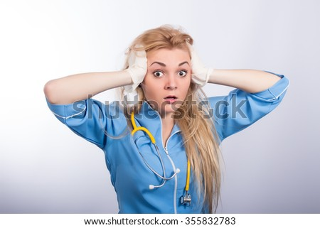 Surprised woman doctor on light  background - stock photo