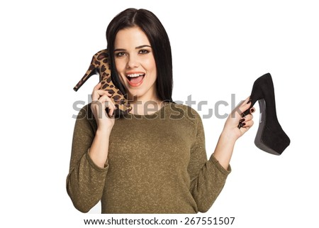 Surprised woman holding a shoe next to her ear, pretending to talk. Gorgeous white caucasian female model isolated on white background. - stock photo