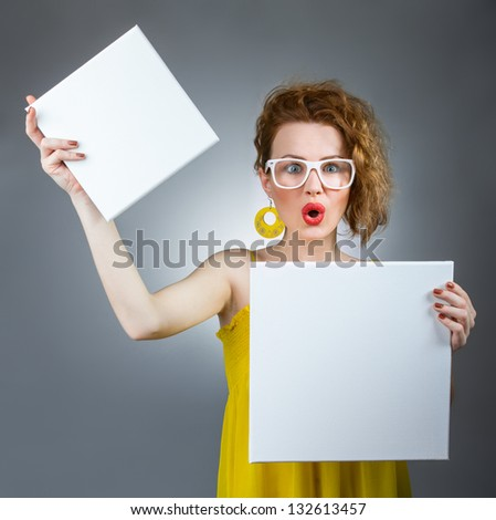 Surprised woman holding white board. Funny gilr with blank panel - stock photo