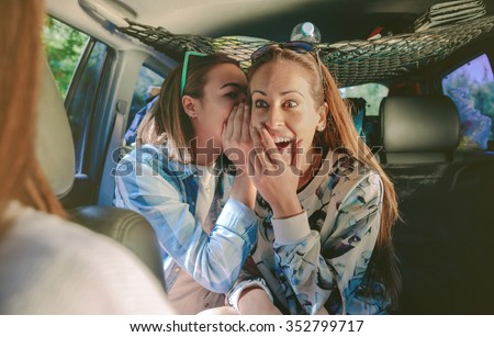 Surprised woman laughing to listening gossip of her friend sitting in rear seat of car - stock photo