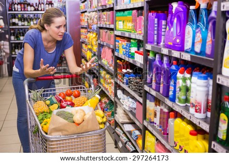 Surprised woman looking at product on shelf at supermarket - stock photo