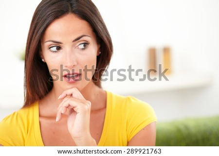 Surprised woman looking away while contemplating with one hand on her chin - copy space - stock photo