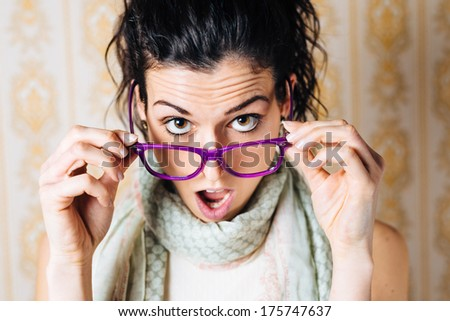 Surprised woman looking over her glasses. Beautiful jaw dropped girl with modern eyewear. - stock photo