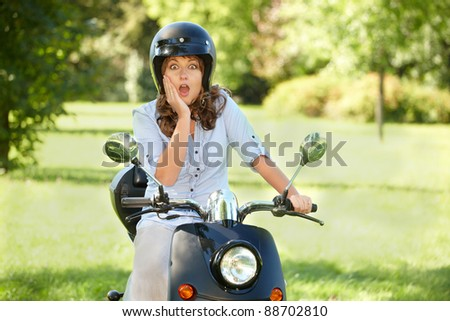 surprised woman oman riding retro motorbike scooter - stock photo