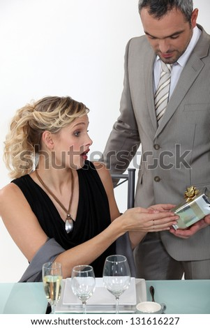 Surprised woman receiving a gift from her boyfriend - stock photo