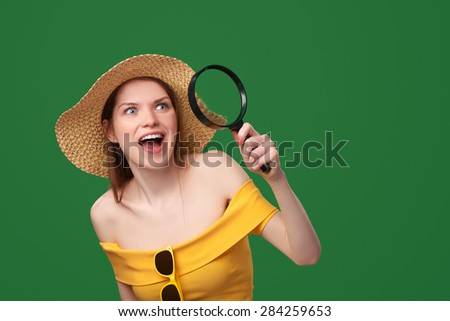 Surprised woman wearing bright yellow dress and summer straw hat looking through the magnifying glass at the blank copy space, over green background - stock photo