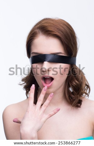 Surprised woman with black blindfold over gray background - stock photo