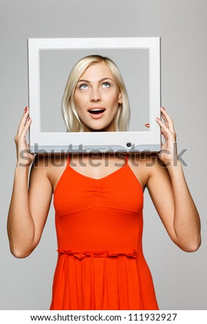 Surprised young blond female looking through the TV / computer screen frame, looking up, over gray background - stock photo