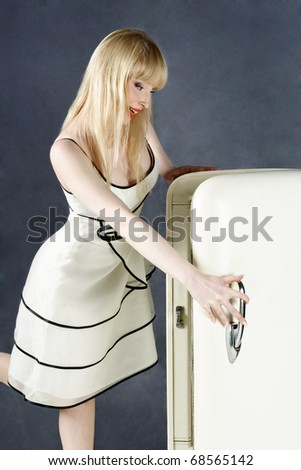 Surprised young blond woman looking into open refrigerator - stock photo