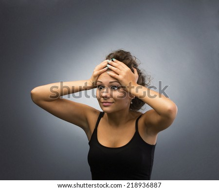 surprised young brunette woman holding her head, isolated on grey light background - stock photo