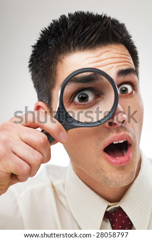 surprised young business man looking through loupe close up - stock photo