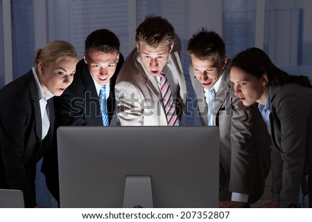 Surprised young business people looking at computer monitor in office - stock photo