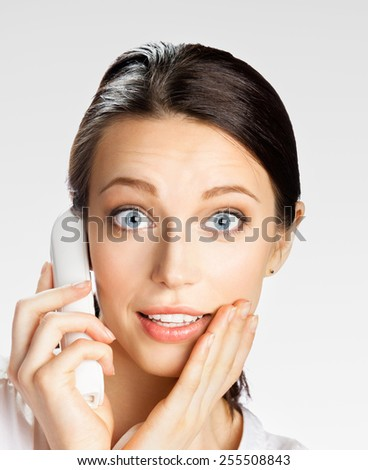 Surprised young businesswoman with phone, on grey - stock photo