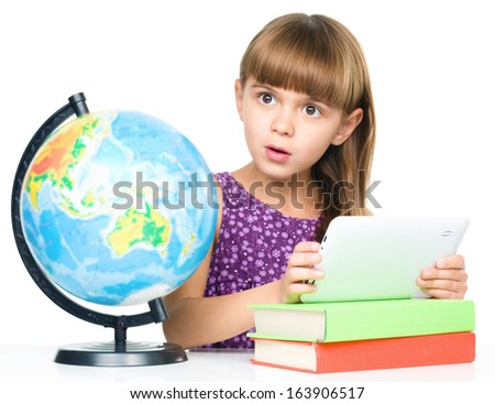 Surprised young girl is using tablet while studying geography, isolated over white - stock photo