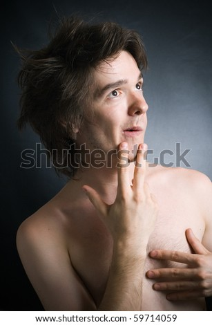 Surprised young the man on a dark background. - stock photo