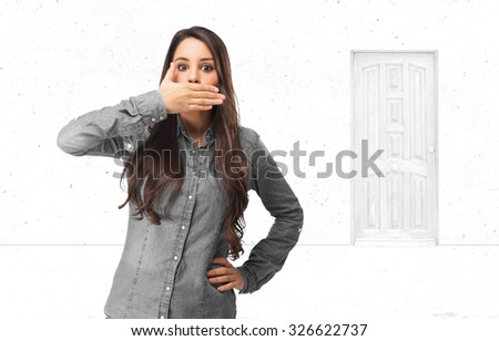 surprised young woman covering mouth - stock photo