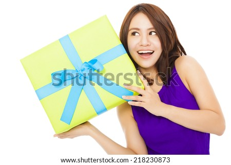 surprised young woman holding a gift box over white background - stock photo