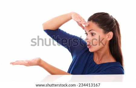 Surprised young woman holding palms up in white background - copyspace - stock photo