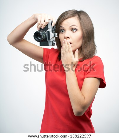 Surprised young woman in a red shirt. Holds the camera. On a gray background - stock photo