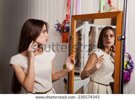 surprised young woman in light dress looking in the mirror - stock photo