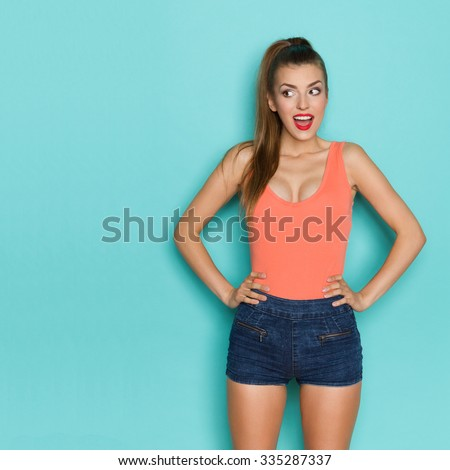 Surprised young woman in orange shirt and jeans shorts standing with hands on hip and looking away. Three quarter length studio shot on teal background. - stock photo