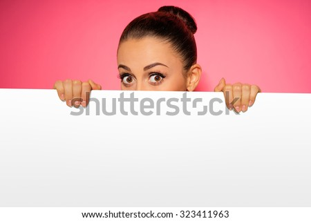 Surprised young woman looking out of the blank with copy space. Pink background. - stock photo