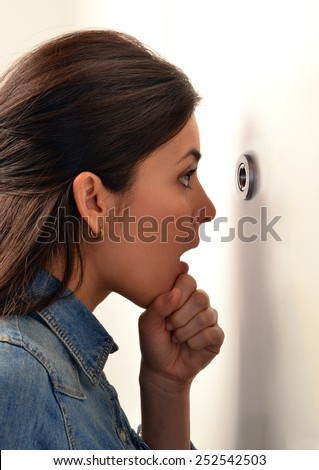 Surprised young woman looking out through the peephole of her front door. - stock photo