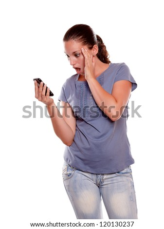 Surprised young woman reading a message on cellphone standing over white background - stock photo