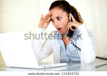 Surprised young woman reading on laptop screen while conversing on phone - stock photo