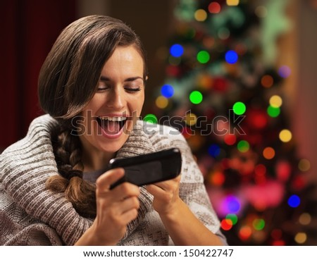 Surprised young woman reading sms near christmas tree - stock photo