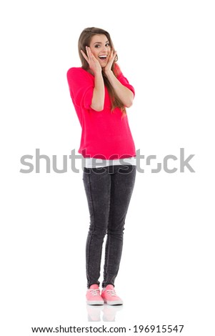 Surprised young woman shouting and holding head. Full length studio shot isolated on white. - stock photo