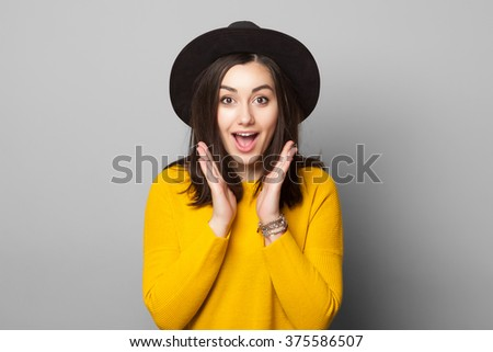 Surprised young woman wearing warm yellow clothes and stylish hat over gray background - stock photo