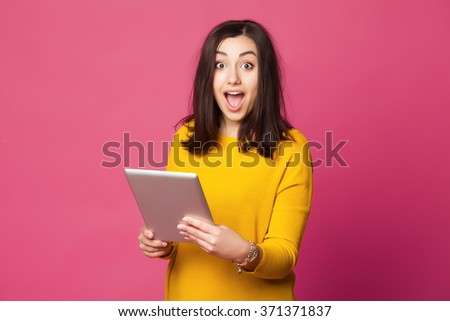 Surprised young woman wearing yellow clothes shcoked while holding tablet pc isolated on pink background - stock photo