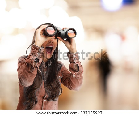 surprised young woman with binoculars - stock photo