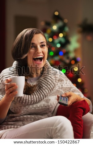 Surprised young woman with cup of hot chocolate watching tv - stock photo