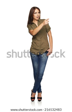 Surprised young woman with mouth opened pointing to the side at blank copy space, standing in full length, over white background - stock photo
