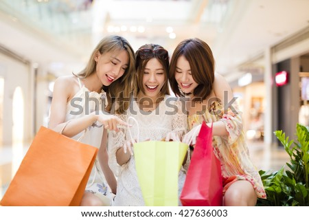 Surprised young women looking the shopping  bags  - stock photo