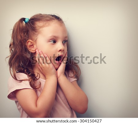 Surprising kid girl with opened mouth and hand near face looking on. Toned portrait. Closeup - stock photo