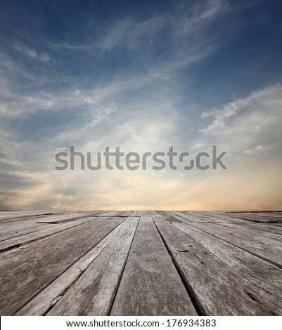 Surreal cloudy evening sky in the horizon of an empty grungy timber deck platform.  - stock photo